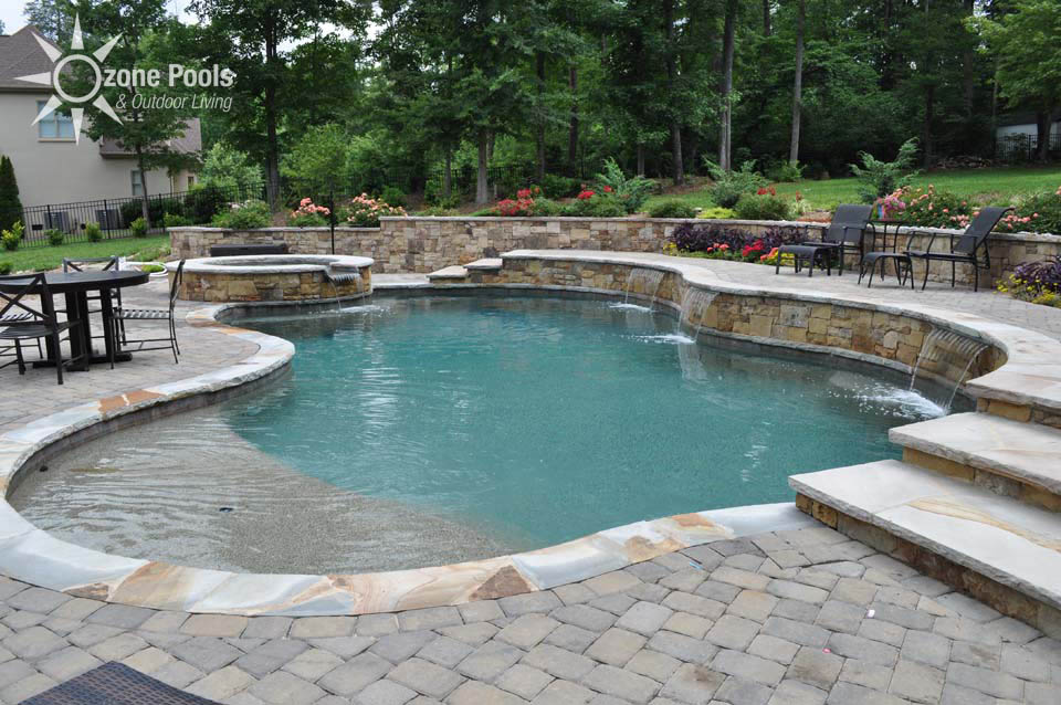 freeform pool spa with stone retaining wall